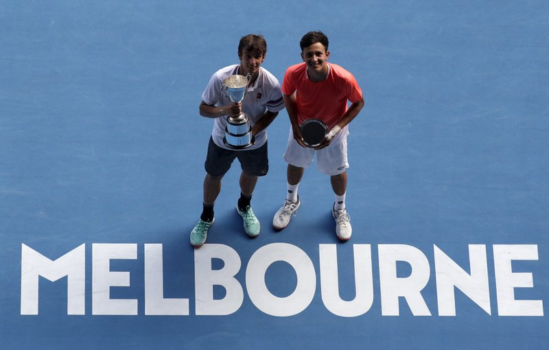 Italy's Lorenzo Musetti, left, holds his trophy after defeating United States' Emilio Nava, right, in the boy's singles final at the Australian Open tennis championships in Melbourne, Australia, Saturday, Jan. (AP Photo/Kin Cheung)