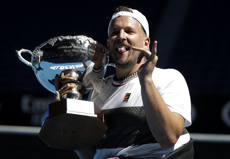 Australia's Dylan Alcott celebrates with his trophy after defeating United States' David Wagner in the men's quad wheelchair final at the Australian Open tennis championships in Melbourne, Australia, Saturday, Jan. (AP Photo/Mark Schiefelbein)
