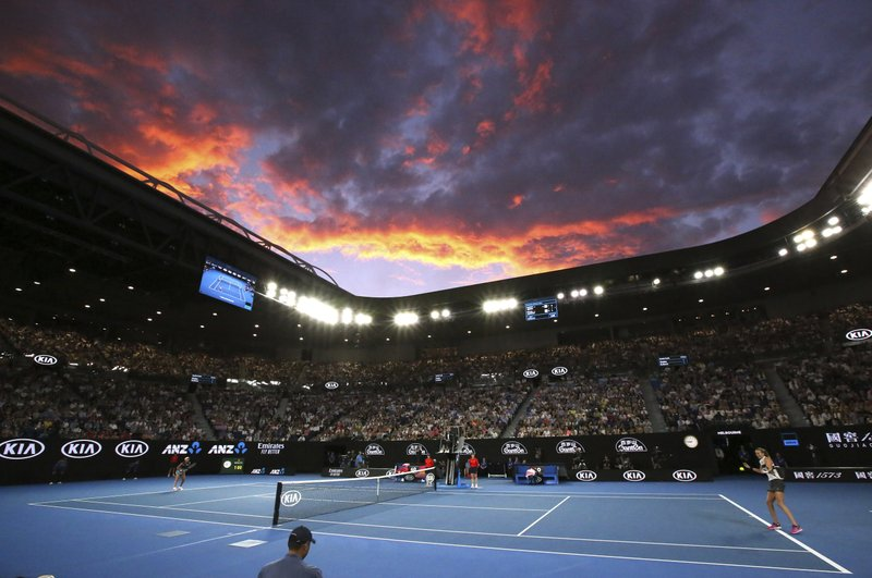 The sun sets behind Melbourne Park as Petra Kvitova, right, of the Czech Republic hits a forehand to Japan's Naomi Osaka during the women's singles final on Rod Laver Arena at the Australian Open tennis championships in Melbourne, Australia, Saturday, Jan. (AP Photo/Aaron Favila)