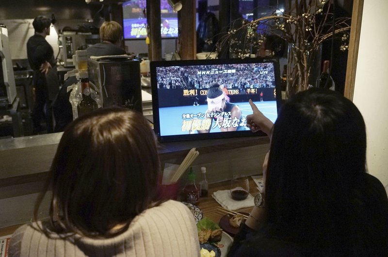 Customers at a restaurant in Tokyo watch the TV monitor at the end of the Australian Open tennis women's final between Naomi Osaka of Japan and Petra Kvitova of Czech Republic Saturday, Jan. (AP Photo/Eugene Hoshiko)
