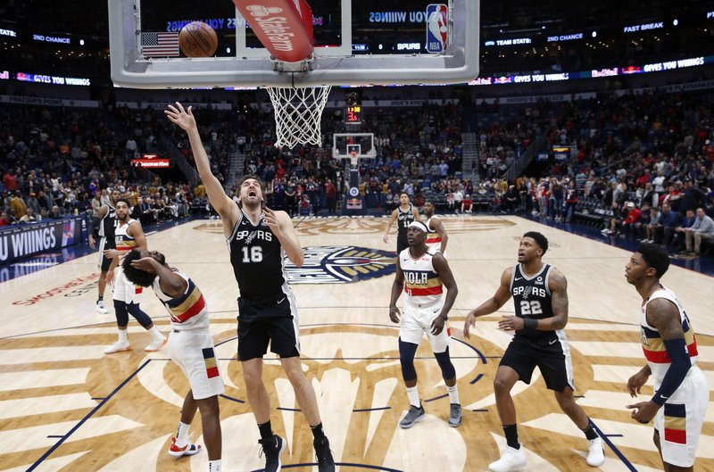 San Antonio Spurs center Pau Gasol (16) goes to the basket against New Orleans Pelicans forward Solomon Hill, left, in the first half of an NBA basketball game in New Orleans, Saturday, Jan. (AP Photo/Gerald Herbert)