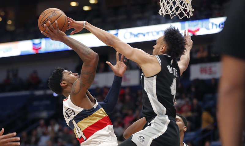 New Orleans Pelicans guard Elfrid Payton), left, goes to the basket against San Antonio Spurs guard Derrick White, right, in the first half of an NBA basketball game in New Orleans, Saturday, Jan. (AP Photo/Gerald Herbert)