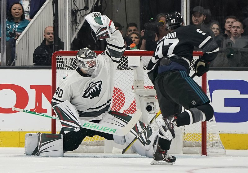 Central Division's Devan Dubnyk, left, of the Minnesota Wild, defends the net against Pacific Division's Connor McDavid, of the Edmonton Oilers, during the second half of a semifinal of the NHL hockey All-Star Game in San Jose, Calif. (AP Photo/Tony Avelar)