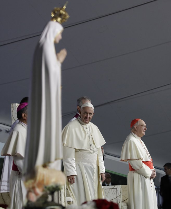 Pope Francis is flanked by Cardinal Kevin Farrell as he arrives on the altar during a vigil at Campo San Juan Pablo II in Panama City, Saturday, Jan. (AP Photo/Alessandra Tarantino)