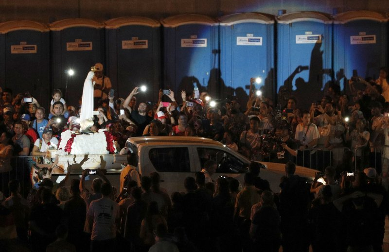 An image of the Virgin Mary is carried on the bed of a pick-up truck during a vigil with Pope Francis at Campo San Juan Pablo II in Panama City, Saturday, Jan. (AP Photo/Rebecca Blackwell)