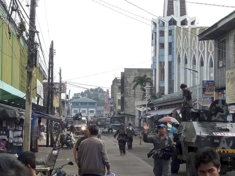 In this photo provided by WESMINCOM Armed Forces of the Philippines, soldiers and police cordon off the area after two bombs exploded outside a Roman Catholic cathedral (background right) in Jolo, the capital of Sulu province in the southern Philippines where militants are active, Sunday, Jan. (WESMINCOM Armed Forces of the Philippines Via AP)