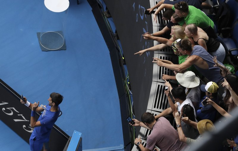 Serbia's Novak Djokovic takes a selfie with spectators as he practices on Rod Laver Arena ahead of his men's singles final against Spain's Rafael Nadal at the Australian Open tennis championships in Melbourne, Australia, Sunday, Jan. (AP Photo/Mark Schiefelbein)