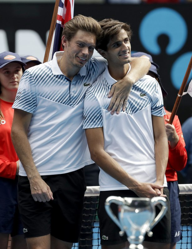 France's Pierre-Hugues Herbet, right, and compatriot Nicolas Mahut embrace after defeating Finland's Henri Kontinen and Australia's John Peers in the men's doubles final at the Australian Open tennis championships in Melbourne, Australia, Sunday, Jan. (AP Photo/Aaron Favila)