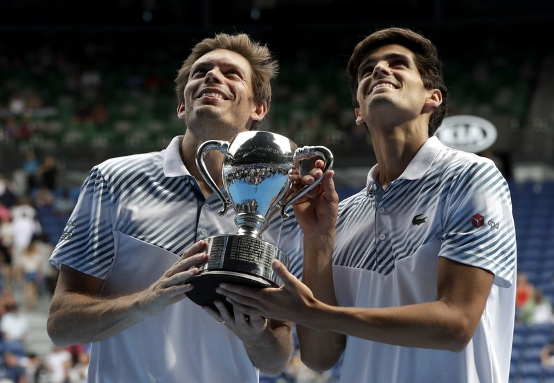 France's Pierre-Hugues Herbet, right, and compatriot Nicolas Mahut hold their trophy after defeating Finland's Henri Kontinen and Australia's John Peers in the men's doubles final at the Australian Open tennis championships in Melbourne, Australia, Sunday, Jan. (AP Photo/Kin Cheung)
