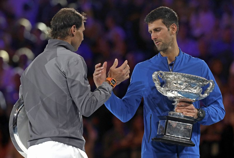 Serbia's Novak Djokovic, right, shakes hands with Spain's Rafael Nadal on the podium after winning the men's singles final at the Australian Open tennis championships in Melbourne, Australia, Sunday, Jan. (AP Photo/Kin Cheung)