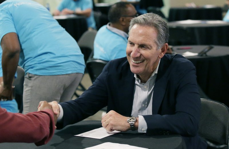 FILE - In this May 19, 2017, file photo, Starbucks CEO Howard Schultz, right, shakes hands with a job seeker during the Opportunity Fair and Forum employment event in Dallas. (AP Photo/LM Otero, File)