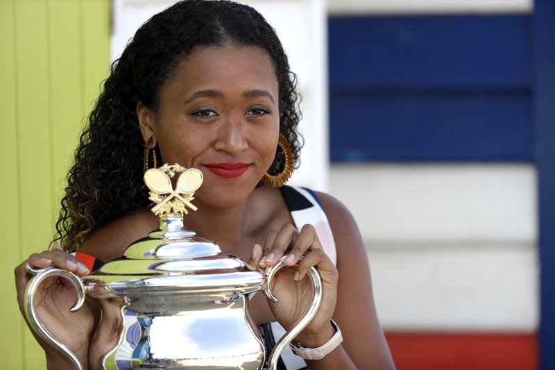 Japan's Naomi Osaka poses with her trophy the Daphne Akhurst Memorial Cup at Melbourne's Brighton Beach following her win over Petra Kvitova of the Czech Republic in the women's singles final at the Australian Open tennis championships in Melbourne, Australia, Sunday, Jan. (AP Photo/Aaron Favila)