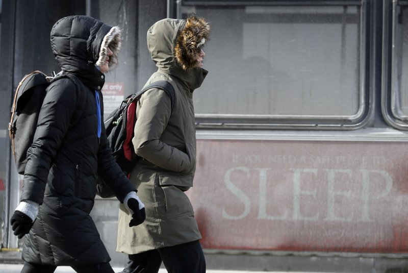People are bundled up against the cold in downtown Chicago, Sunday, Jan. 27, 2019. More than with many snowstorms Chicagoans have endured in recent history, where you live will greatly impact how much snow you arise to Monday morning, forecasters said. (AP Photo/Nam Y. Huh)