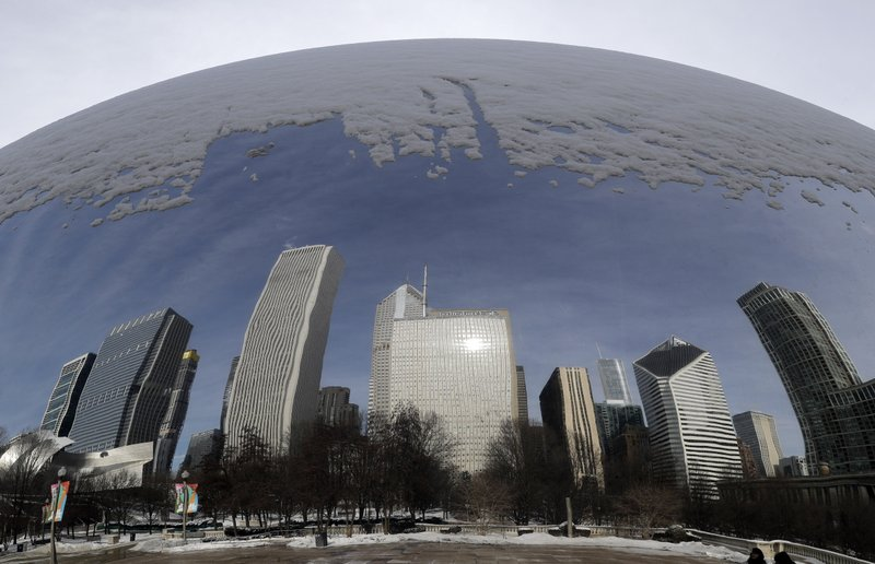 Reflections of a snowy city are seen in the 110-ton stainless steel Anish Kapoor sculpture called 'Cloud Gate' and nicknamed 'The Bean' at Millennium Park in Chicago, Sunday, Jan. (AP Photo/Nam Y. Huh)