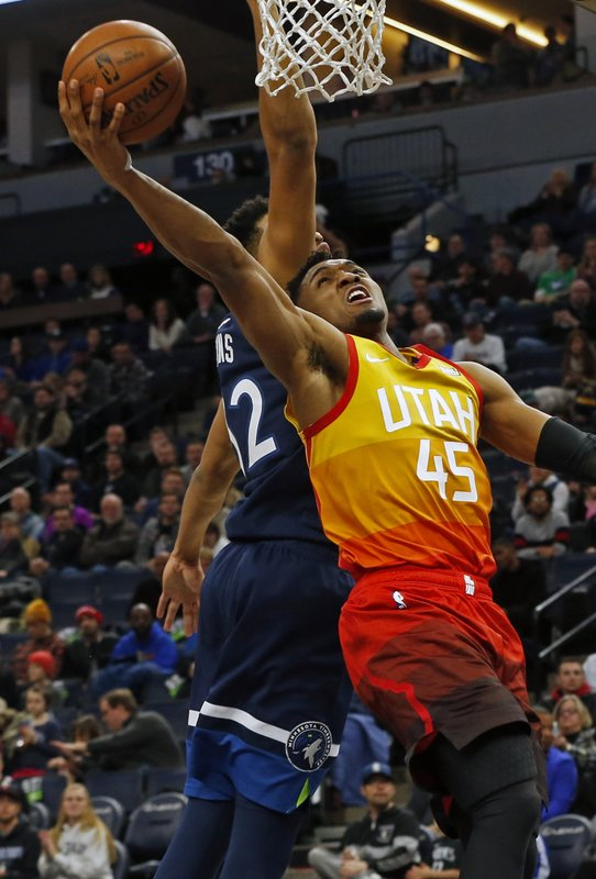 Utah Jazz's Donovan Mitchell, right, lays up a shot as Minnesota Timberwolves' Karl-Anthony Towns defends in the first half of an NBA basketball game Sunday, Jan. (AP Photo/Jim Mone)
