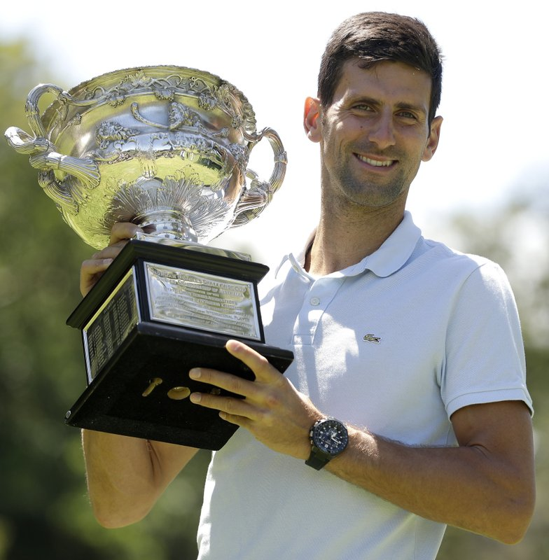 Serbia's Novak Djokovic poses with his trophy, the Norman Brookes Challenge Cup, at Melbourne's Royal Botanic Gardens following his win over Rafael Nadal of Spain in the men's singles final at the Australian Open tennis championships in Melbourne, Australia, Monday, Jan. (AP Photo/Mark Schiefelbein)
