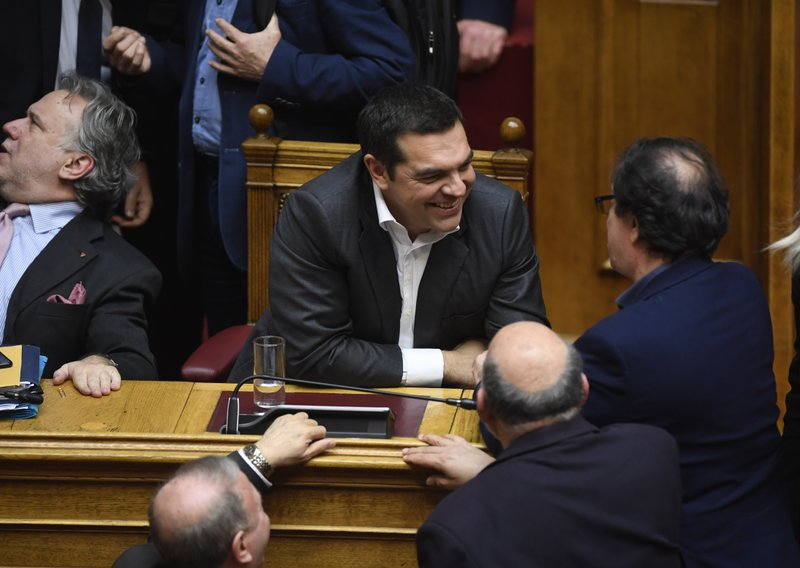 Greece's Prime Minister Alexis Tsipras, centre, is congratulated by aides following a vote that ratified the Prespa Agreement at the parliament in Athens, Friday, Jan. (AP Photo/Michael Varaklas)