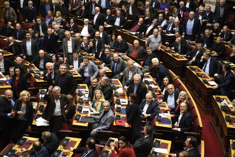 Members of the Greek parliament debate the Prespa Agreement in Athens, Friday, Jan. 25, 2019. Greek lawmakers have ratified the agreement for the country to drop its objections to neighbouring Macedonia joining NATO if the small country's name is changed to North Macedonia. (AP Photo/Michael Varaklas)