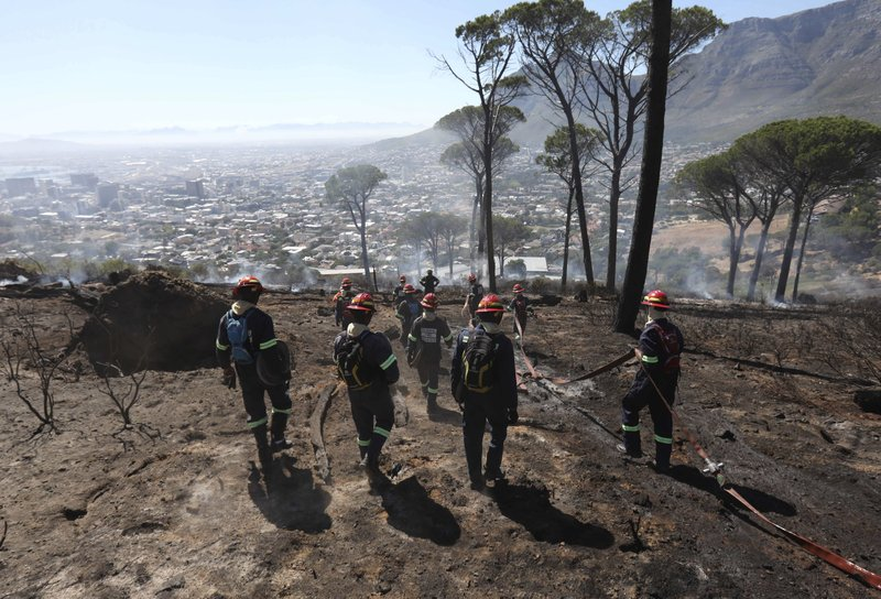 Fire officers during the clean up operation on Signal Hill, Cape Town, Monday Jan. 28, 2019, after an overnight fire around the city's iconic Lion's Head. (AP Photo)