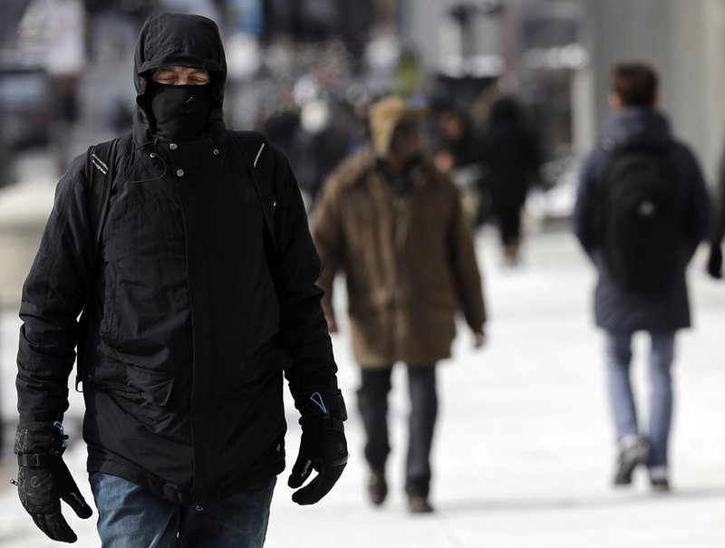 A man is bundled up against the cold in downtown Chicago, Sunday, Jan. 27, 2019. More than with many snowstorms Chicagoans have endured in recent history, where you live will greatly impact how much snow you arise to Monday morning, forecasters said. (AP Photo/Nam Y. Huh)