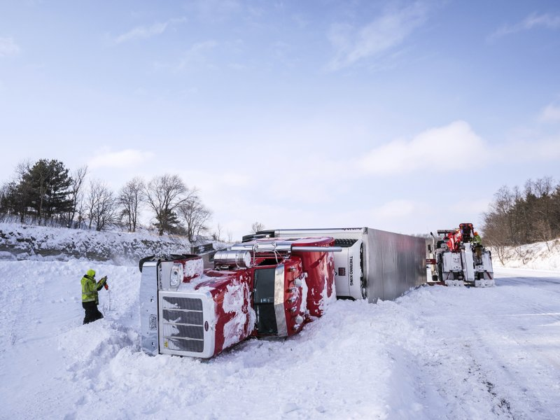 Tow truck personnel work to remove an overturned semi in the median of Interstate 90 at mile marker 218 near the U. (Joe Ahlquist/The Rochester Post-Bulletin via AP)
