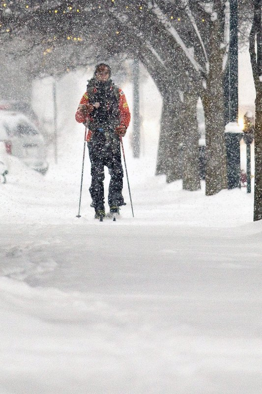 Mike Powers cross country skis to work in downtown Traverse City, Mich, as snow blankets the Grand Traverse area on Monday, Jan 28, 2019. (Jan-Michael Stump/Traverse City Record-Eagle via AP)