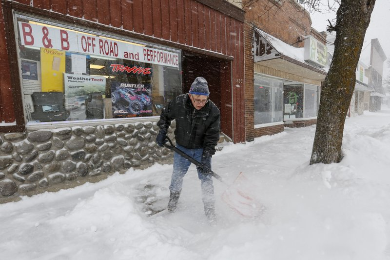 Bill Stalvey, of Manitowoc, clears the sidewalk in front of his shop, B & B Off Road and Performance RC, during a winter storm Monday, Jan. (Joshua Clark/The Post-Crescent via AP)