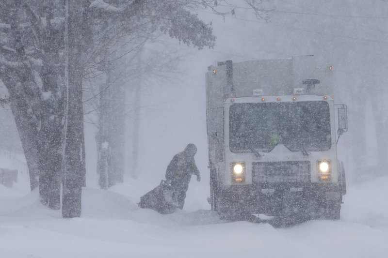 An employee of Pozorski Hauling & Recycling collects trash during a snowstorm Monday, Jan. 28, 2019, in Manitowoc, Wis. (Joshua Clark/The Post-Crescent via AP)