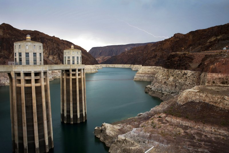 FILE - In this July 28, 2014, file photo, lightning strikes over Lake Mead near Hoover Dam that impounds Colorado River water at the Lake Mead National Recreation Area in Arizona. (AP Photo/John Locher, File)