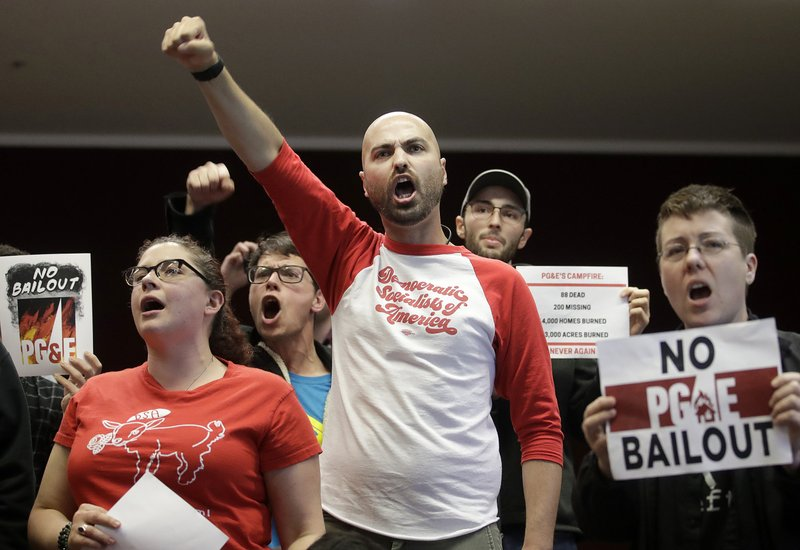Brandon Harami, center, and others yell during a California Public Utilities Commission meeting in San Francisco, Monday, Jan. (AP Photo/Jeff Chiu)