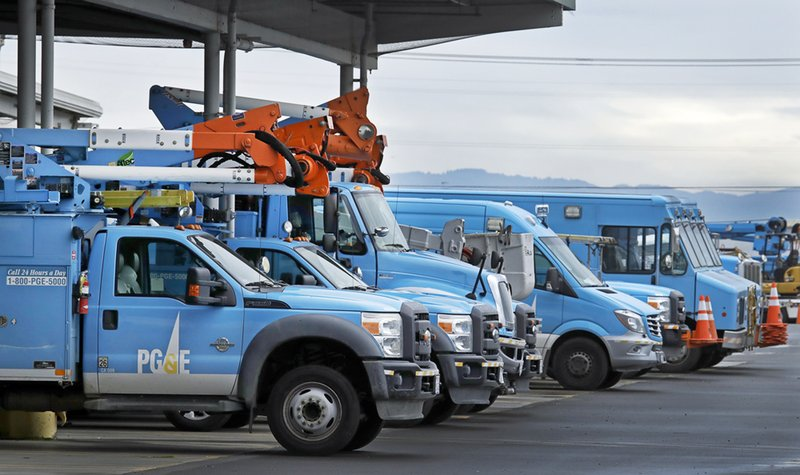 FILE - This Jan. 14, 2019 file photo shows Pacific Gas & Electric vehicles parked at the PG&E Oakland Service Center in Oakland, Calif. (AP Photo/Ben Margot, File)