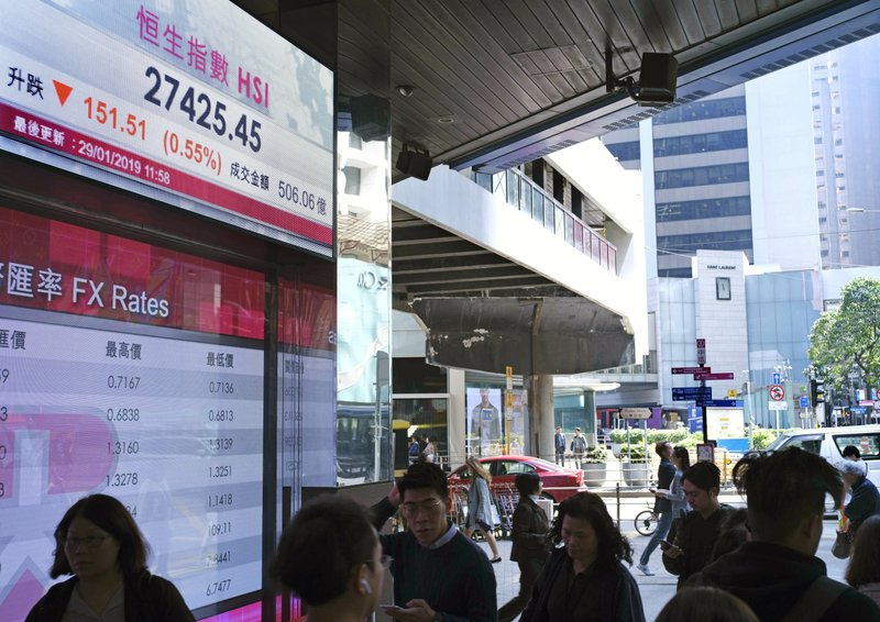 People walk past an electronic board showing Hong Kong share index outside a local bank in Hong Kong, Tuesday, Jan. (AP Photo/Vincent Yu)