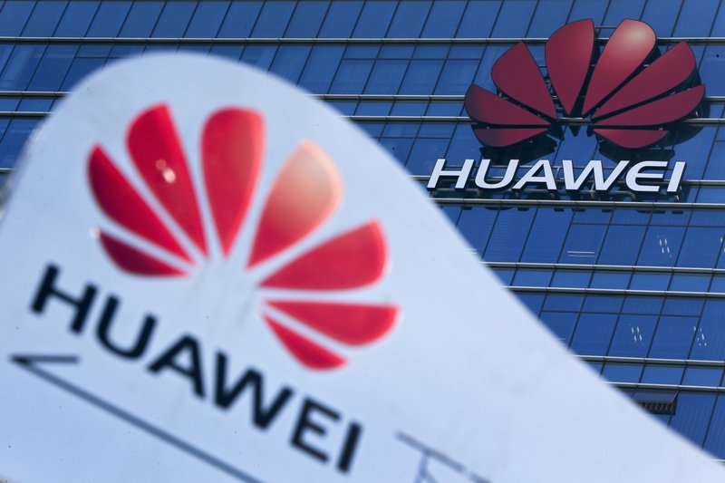 FILE - This Tuesday, Dec. 18, 2018, file photo, shows company signage on display near the Huawei office building at its research and development center in Dongguan, in south China's Guangdong province. (AP Photo/Andy Wong, File)