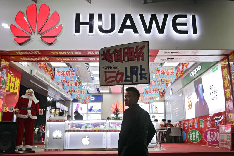 FILE - In this Dec. 18, 2018, file photo, a worker holds a sign promoting a sale for Huawei 5G internet services at a mobile phone retail shop in Shenzhen in south China's Guangdong province. (AP Photo/Andy Wong, File)