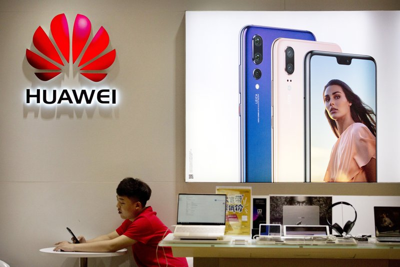 FILE - In this July 4, 2018, file photo, a sales clerk looks at his smartphone in a Huawei store at a shopping mall in Beijing. (AP Photo/Mark Schiefelbein, File)