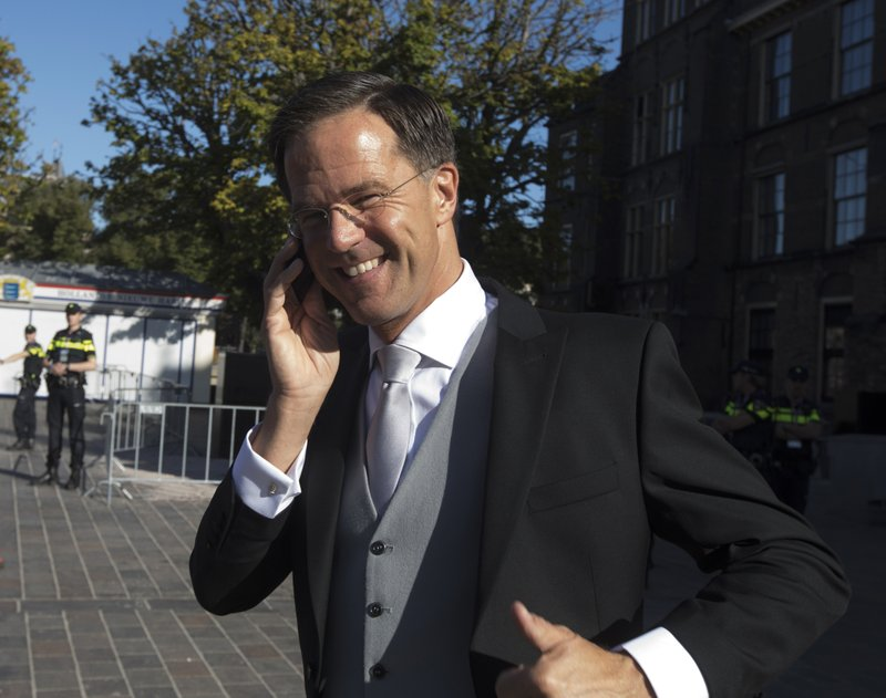 In this Tuesday Sept. 18, 2018, file image Dutch Prime Minister Mark Rutte flashes a thumbs up as he talks on in his phone in The Hague, Netherlands, prior to a ceremony marking the opening of the parliamentary year with a speech by King Willem-Alexander outlining the government's budget plans for the year ahead. (AP Photo/Peter Dejong)