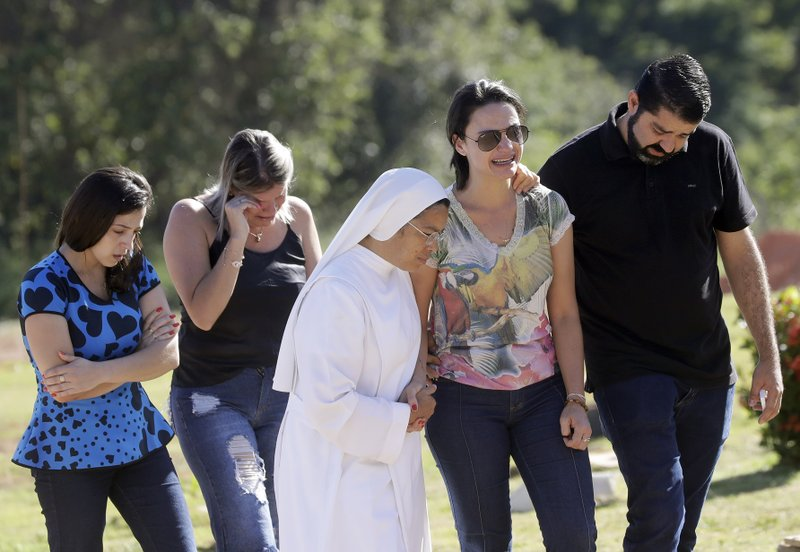 Friends and relatives attend the burial of Vale SA employee Edgar Carvalho Santos, victim of the collapsed dam in Brumadinho, Brazil, Tuesday, Jan. (AP Photo/Andre Penner)