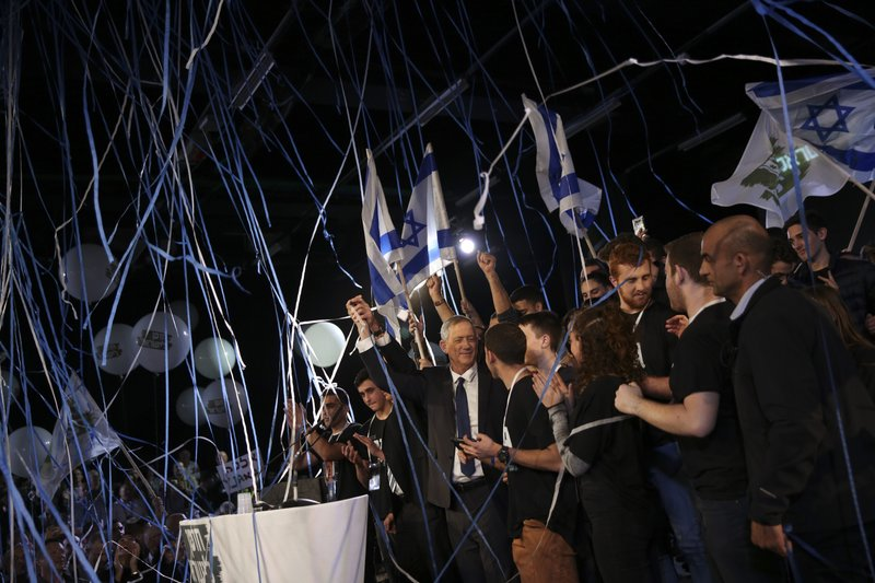 Retired Israeli military chief Benny Gantz, center, raises his hand during the official launch of his election campaign for the April 2019 elections, in Tel Aviv, Tuesday, Jan. (AP Photo/Oded Balilty)