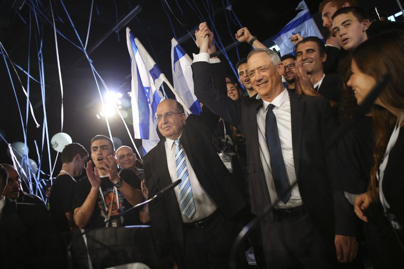 Retired Israeli military chief Benny Gantz, right, and also retired military chief Moshe Yaalon raise hands during the official launch of his election campaign for the April 2019 elections, in Tel Aviv, Tuesday, Jan. (AP Photo/Oded Balilty)