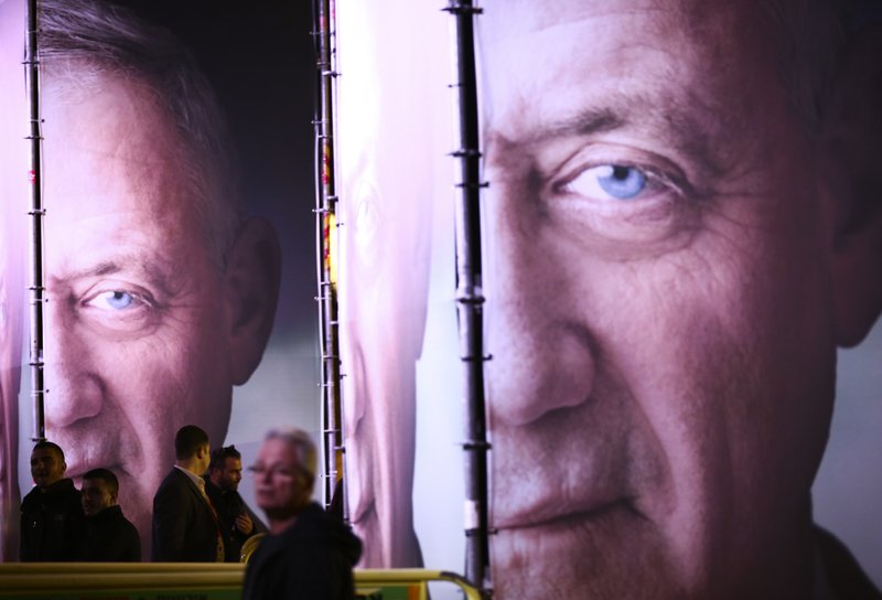 People walk by posters of retired Israeli military chief Benny Gantz before the official launch of his election campaign for the April 2019 elections, in Tel Aviv, Tuesday, Jan. (AP Photo/Oded Balilty)