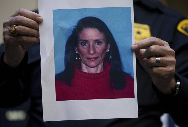 A Houston Police officer holds up the photo of one of the suspects,  Rhogena Nicholas, during a news conference at Memorial Hermann Hospital on Tuesday, Jan. (Godofredo A. Vasquez/Houston Chronicle via AP)