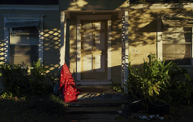 Bullet holes can be seen on the front entrance of a home, where five Houston Police officers were shot while serving a warrant Tuesday, Jan. (Godofredo A. Vasquez/Houston Chronicle via AP)/Houston Chronicle via AP)
