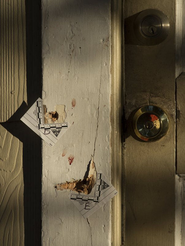 Seventeen bullet holes can be seen on the front entrance of a home, where five Houston Police officers were shot while serving a warrant Tuesday, Jan. (Godofredo A. Vasquez/Houston Chronicle via AP)