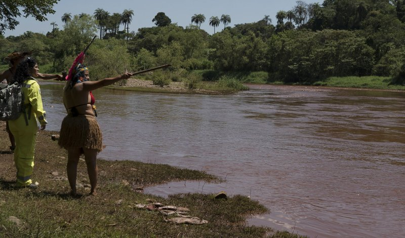 A Pataxo Ha-ha-hae indigenous woman points toward the Paraopeba River as she speaks to a member of the Brazilian Environmental Institute (IBAMA) in her village, in Brumadinho, Brazil, Tuesday, Jan. (AP Photo/Leo Correa)