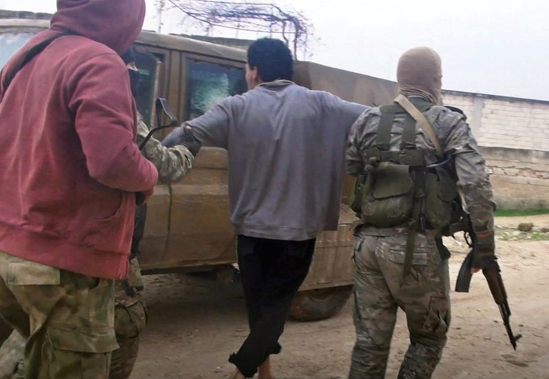 This photo released Dec. 16, 2018 by the al-Qaida-affiliated Ibaa News Agency, purports to show al-Qaida-linked Hayat Tahrir al-Sham, or HTS, militants detaining a member of the Islamic State group in the countryside of Idlib, Syria. (Ibaa News Agency, via AP)