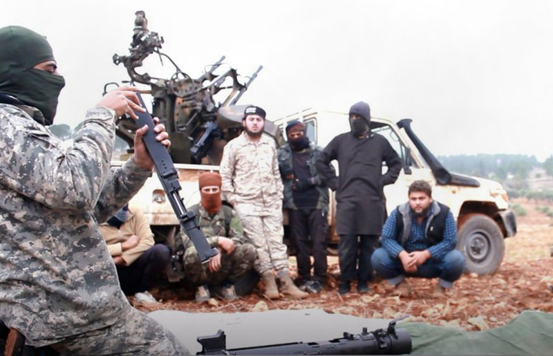 This photo released Tuesday, Nov. 13, 2018 by the al-Qaida-affiliated Ibaa News Agency, shows al-Qaida-linked militants learning how to use a heavy weapon in the countryside of Idlib, Syria. (Ibaa News Agency, via AP)