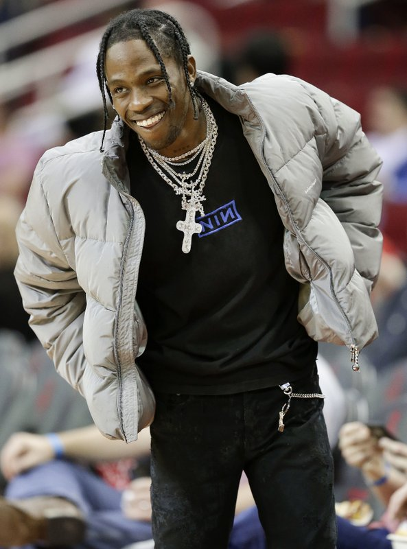 FILE - In this Feb. 9, 2018, file photo, hip hop artist Travis Scott watches warmups before an NBA basketball game between the Houston Rockets and the Denver Nuggets, in Houston. (AP Photo/Eric Christian Smith, File)