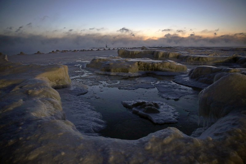 Ice forms along the shore of Lake Michigan before sunrise, Wednesday, Jan. 30, 2019, in Chicago. A deadly arctic deep freeze enveloped the Midwest with record-breaking temperatures on Wednesday, triggering widespread closures of schools and businesses, and prompting the U. (AP Photo/Kiichiro Sato)