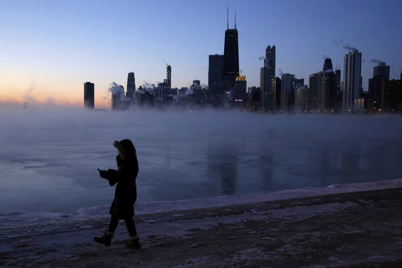 A person walks along the lakeshore, Wednesday, Jan. 30, 2019, in Chicago. A deadly arctic deep freeze enveloped the Midwest with record-breaking temperatures on Wednesday, triggering widespread closures of schools and businesses, and prompting the U. (AP Photo/Kiichiro Sato)