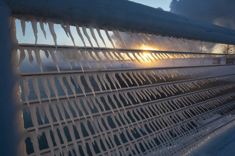 Icicles form on a railing as the sun rises in the harbor in Port Washington, Wis., on Wednesday, Jan. (AP Photo/Jeffrey Phelps)